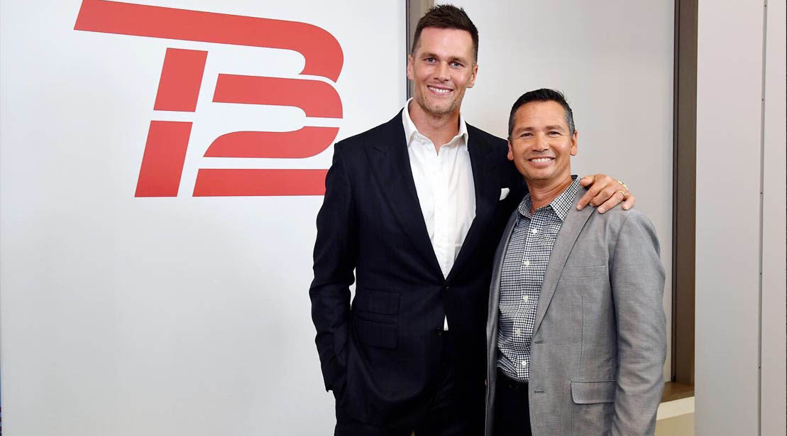 Tom Brady trainer Alex Guerrero standing in front of his gym tb12 helping him train his hamstrings