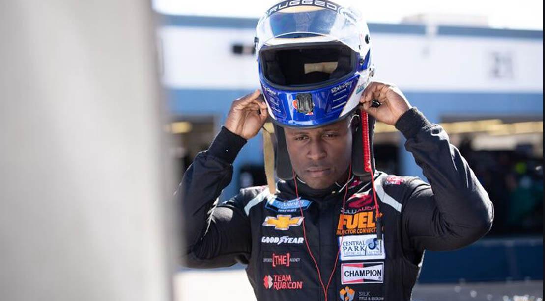 Nascar driver Jessie Iwuji putting on his race car helmet