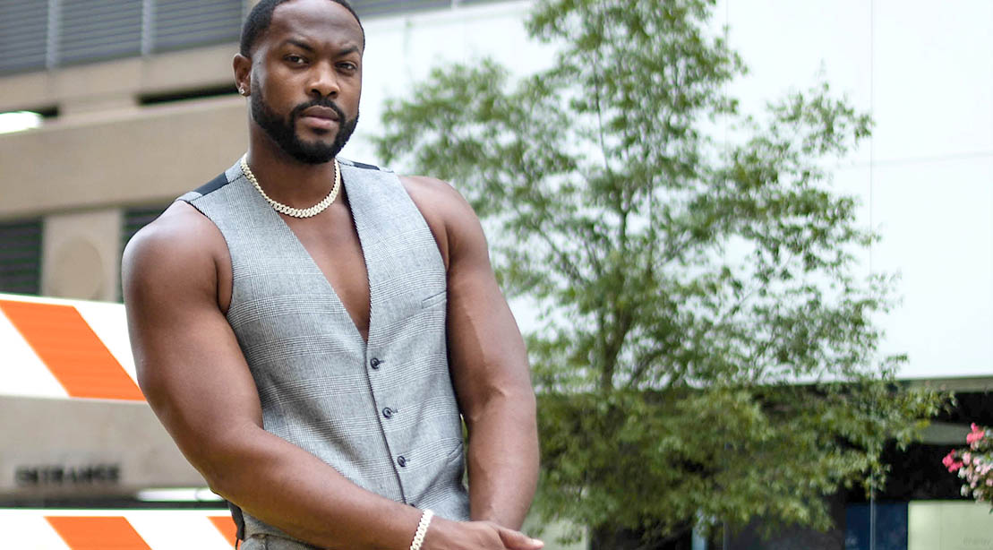 Ser'Darius Blaine wearing a vest and showing his muscular arms in his role in The Big Leap