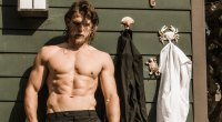 Travis Van Winkle leaning against a house with his shirt off showing his ab muscles