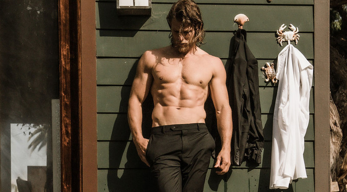 Travis Van Winkle posing against a house with his shirt off and ab muscles